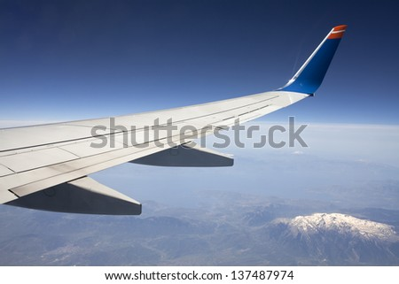 Wing of the plane on blue sky background and snowy mountains below, view from window of a jet plane wing with beautiful weather. - stock photo