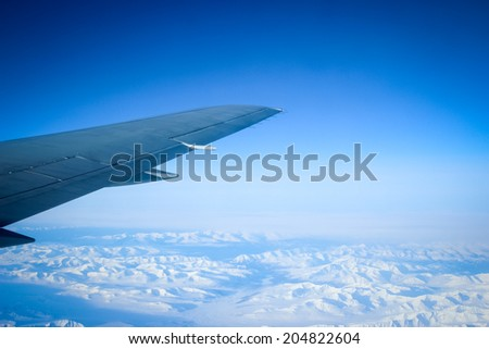 Wing of the plane on blue sky background and snowy mountains, view from window - stock photo