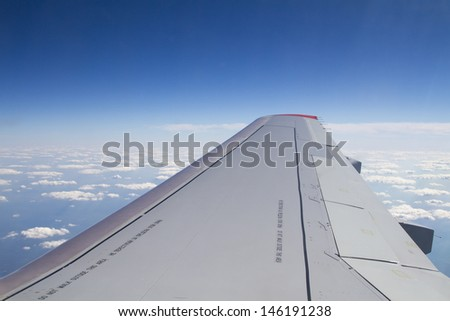 Wing passenger aircraft from a window on the background of the cloudy sky