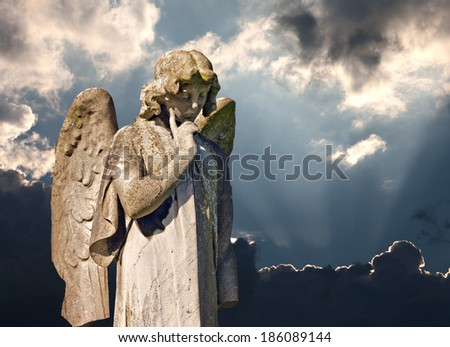 Winged angel statue in ancient graveyard - stock photo