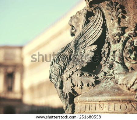 Winged lion statue architectural fragment from Venice. Detail of winged lion in flag mast on Piazza San Marco, Venice, Italy - stock photo