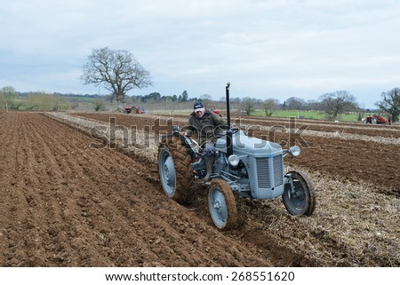 WINGFIELD - APR 4: A tractor pulls a plough through a field on Apr 4, 2015 in Wingfield, UK. Widespread use of tractors emerged during mechanisation of the agricultural industry in the 1950s.