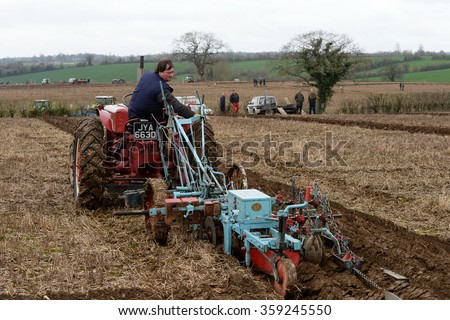 WINGFIELD, UK - APR 4, 2015: A tractor pulls a plough through a field. Widespread use of tractors emerged during the mechanisation of the agricultural industry in the 1950s.