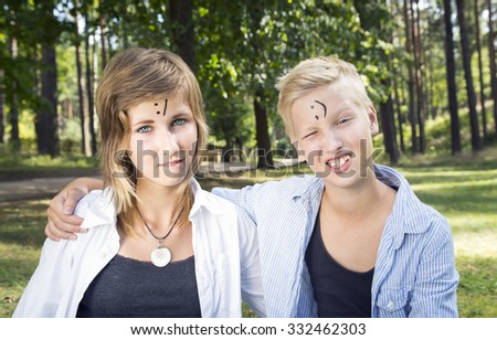 Winking boy and unsure girl sitting on the green grass in nature sunny day. On the forehead shows (drawn) unsure and wink icons. Concept of positive thoughts and emotions.