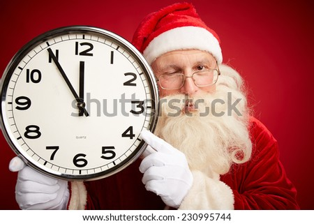 Winking Santa holding clock with five minutes to midnight and pointing at it