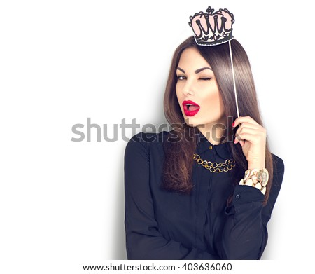 Winking sexy model Girl holding funny paper crown on stick isolated on white background. Joyful young fashion woman with bright make up, red lips and nails - stock photo