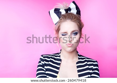Winking young attractive woman  on pink background - stock photo