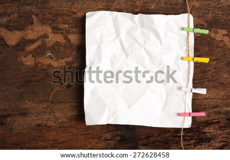 Winkle ripped off paper from notebook page on wood background - stock photo
