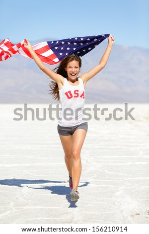 Winner athlete woman running with american flag and USA t-shirt. Runner girl showing winning gesture excited and happy outdoor in desert landscape. Cheerful fitness woman winner cheering, full length. - stock photo