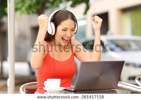 Winner girl euphoric watching a laptop in a coffee shop wearing a red shirt - stock photo