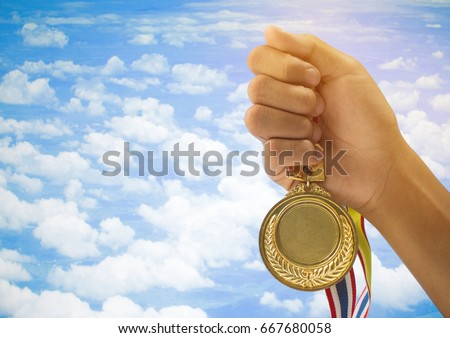 winner hand raised and holding gold medals against blue sky. success award concept