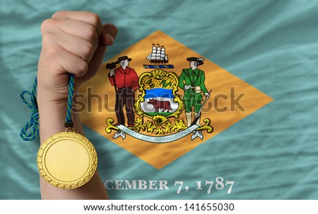 Winner holding gold medal for sport and flag of us state of delaware - stock photo