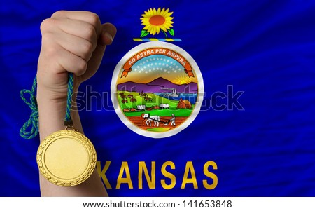 Winner holding gold medal for sport and flag of us state of kansas - stock photo