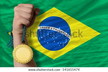 Winner holding gold medal for sport and national flag of brazil
