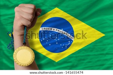 Winner holding gold medal for sport and national flag of brazil - stock photo