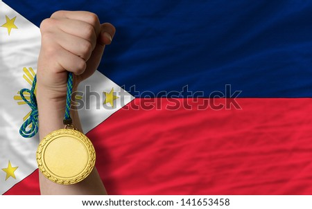 Winner holding gold medal for sport and national flag of philippines - stock photo
