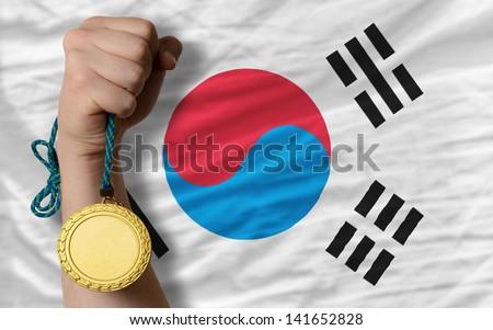 Winner holding gold medal for sport and national flag of south korea - stock photo
