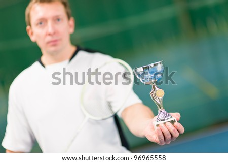 Winner of game and focus on cup which holding in front. - stock photo