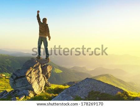 Winner on mountain peak. Active life concept - stock photo
