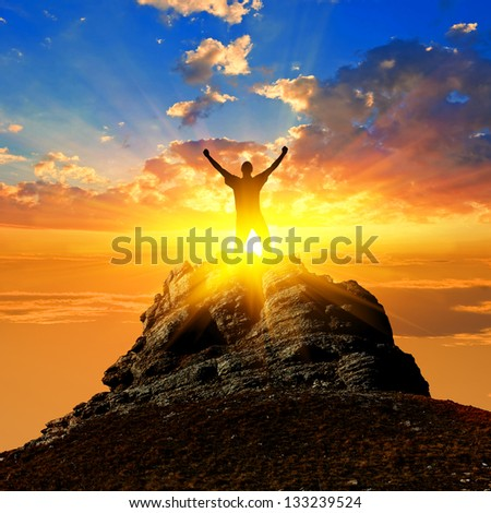 winner silhouette on a mount top - stock photo