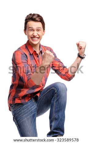 Winner! Studio portrait of excited handsome young man with hands up. Isolated on white.