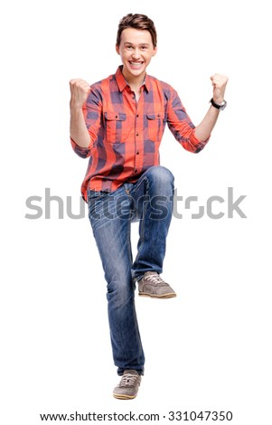 Winner! Studio portrait of excited handsome young man with hands up. Isolated on white. - stock photo