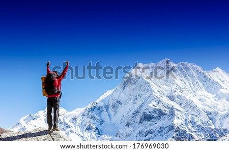 Winner / Success concept. Hiker cheering elated and blissful with arms raised in the sky after hiking to mountain top summit above the clouds