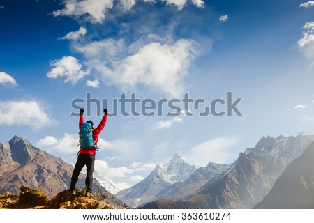 Winner / Success concept. Hiker cheering elated and blissful with arms raised in the sky after hiking to mountain top summit above the clouds - stock photo
