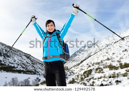 Winner woman hiking success on winter snowy mountains landscape. Winter vacations trip on nature. - stock photo
