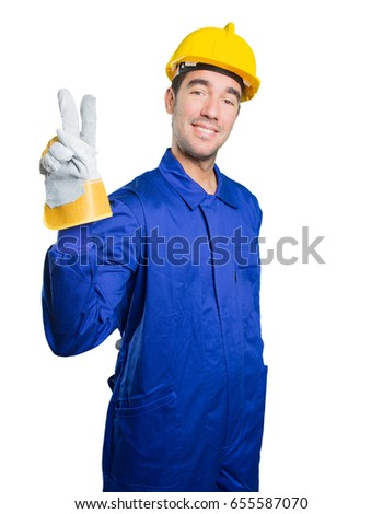 Winner workman with victory gesture on white background