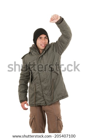 winner young man wearing green winter coat and a beanie with one fist up isolated on white - stock photo