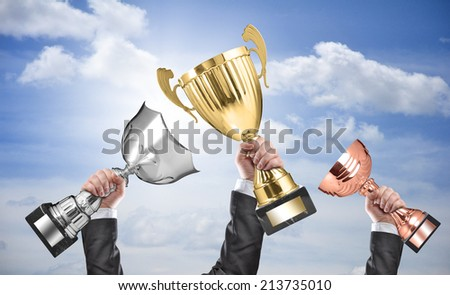 winners holding champion golden, silver and bronze trophies - stock photo
