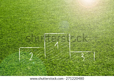 Winners podium sketch on sunny with sun flare artificial green soccer grass background.  - stock photo