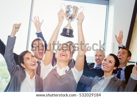 Winning business team with a woman executive holding a gold trophy