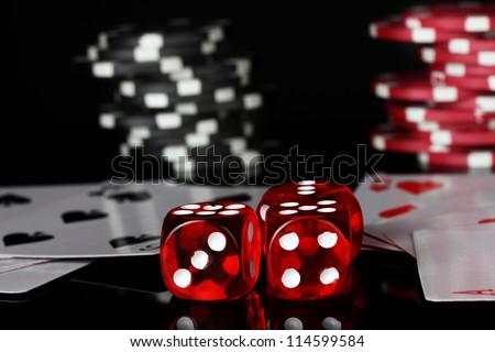 winning combination of playing cards with poker chips and dice on black background - stock photo