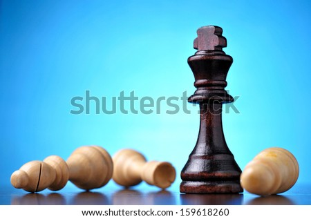 Winning in chess with a black wooden king standing upright over vanquished fallen pawns against a blue background with highlight and copyspace - stock photo