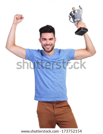 winning young casual man with a big trophy cup and hands in the air - stock photo
