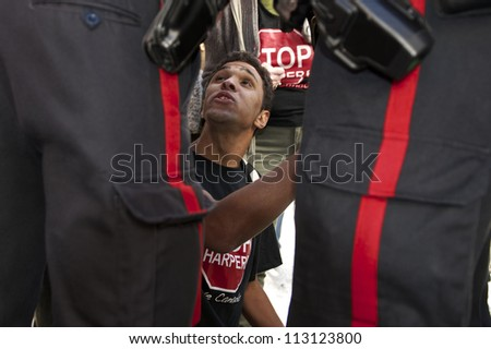 WINNIPEG, CANADA - SEPTEMBER 17: Police detain a protester, Daemon Bath, taking part in Take Back Canada's marking of Occupy Wall Street's first anniversary on September 17, 2012 in Winnipeg. - stock photo