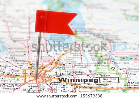 Winnipeg in Manitoba, Canada. Red flag pin on an old map showing travel destination. - stock photo