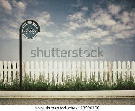wintage picture of bicycle sign and white fence and blue sky - stock photo