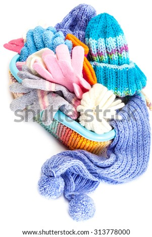 Winter accessory collection. Hat, scarf and mittens in the container, isolated on white background. - stock photo