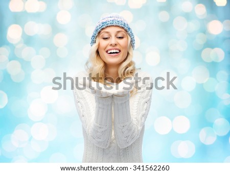 winter, advertisement, christmas and people concept - smiling young woman in winter hat and sweater holding something on her empty palms over blue holidays lights background - stock photo