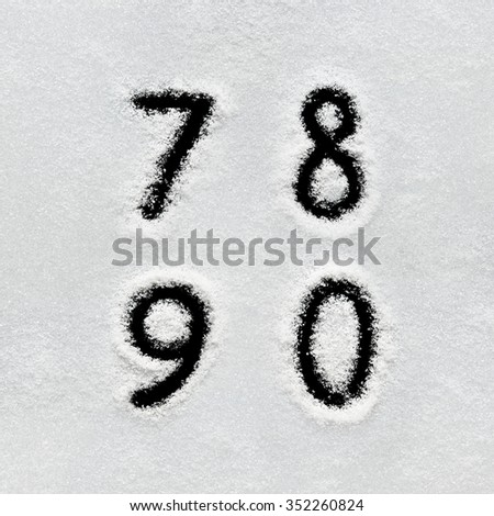 Winter alphabet, symbols and numbers hand written on snow. Black background isolated. 7, 8, 9, 0. - stock photo