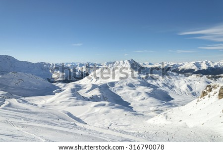 Winter Alpine mountains panorama snow slope with skiing and snowboarding people - stock photo