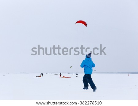 Winter amusements. Small boy running on the snowy frozen river. Snow kite skaters on background. - stock photo