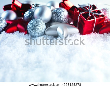 Winter and Christmas background. Beautiful sparkling silver and red Christmas decoration on a white snow background. Ornamental Christmas concept. Close up with copy space. - stock photo