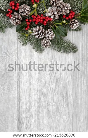 Winter and christmas background border of holly, mistletoe, fir leaf sprigs and snow covered pine cones. - stock photo
