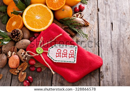 Winter and christmas ingredients still life with oranges, cranberry, nuts and spices and a decorative stocking - stock photo