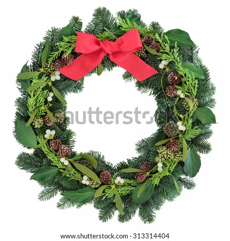Winter and christmas wreath with mistletoe, red bow, pine cones and blue spruce fir over white background. - stock photo