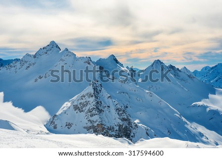 Winter and snow in blue mountains with sky and clouds  - stock photo